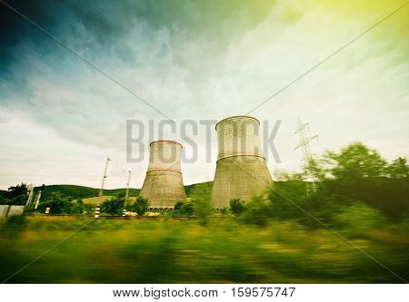 Nuclear power plant as seen from a driving car in green environment