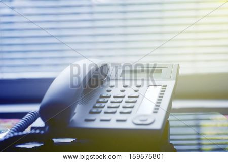 Modern executive VoIP desk phone with traditional corded headset with luxury blinds in the background on a sunny room. Shallow depth of field - focus on the center of the image.