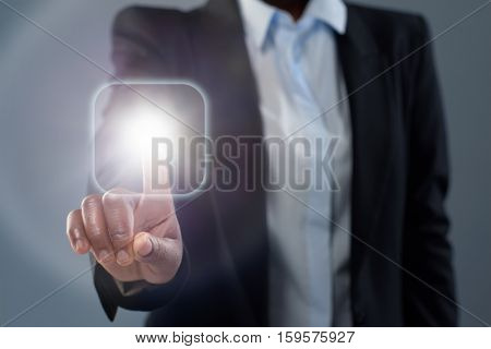 Anonymous african business woman touching a digital interface glowing button
