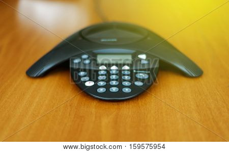 Conference business phone in meeting room on a wooden background in sunny room