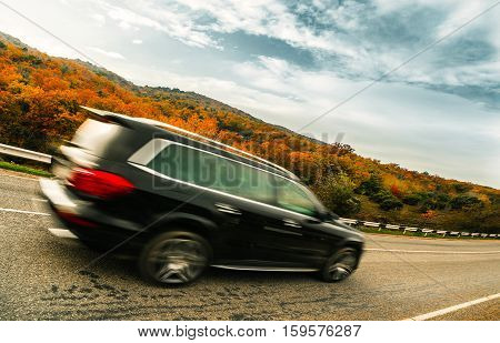 SUV downhills along the autumnal mountain road
