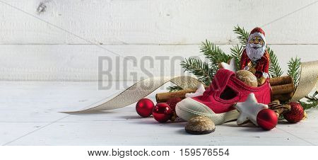 Childrens red shoe filled with sweets cookies and christmas decoration for Nicholas day on the 6th December in Germany white rustic wooden background with bokeh lights and copy space panorama selective focus