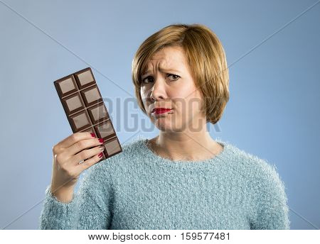 young cute woman holding big chocolate bar with mouth stains and guilty face expression in sugar addiction and ignoring diet concept isolated on blue background