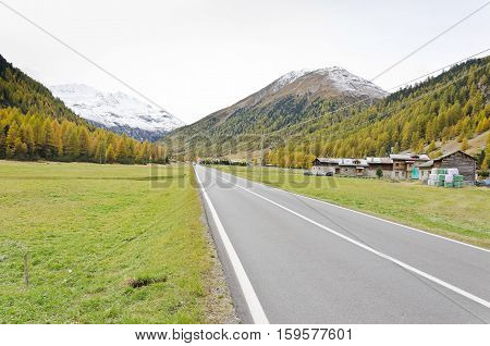 Straight road to the mountain town the gray autumn sky