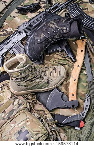 Various army boots,ax,gun,knife,glasses and ammo.Top view.Selective focus