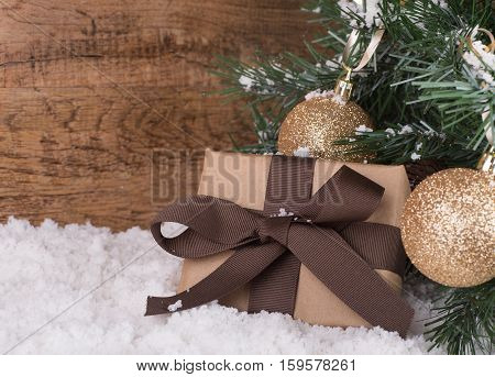 Brown gift box next to a Christmas tree on a wood background