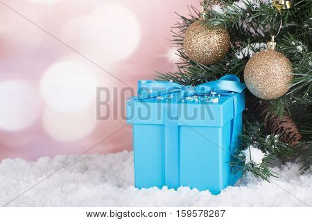 Blue gift box in snow by a Christmas tree with a colorful background