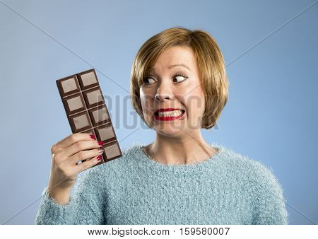 young cute happy woman holding big chocolate bar with mouth stains and crazy excited face expression in sugar addiction and ignoring diet concept isolated on blue background