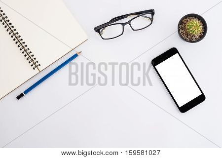 Modern White office desk table with blank screen smartphone eyeglass pencil and leather notebook. Top view with copy space.Office supplies and gadgets on worktable.Working desk table concept.