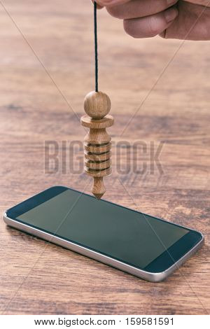 Hand with pendulum dowsing over smart phone to check its quality, dangerous influence or radiation