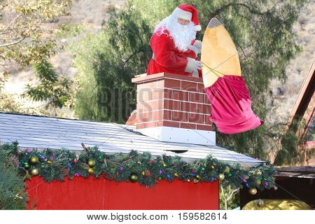 Santa Claus enters a home through the Chimney bringing his bag of toys and gifts for all the good boys and girls.