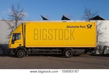 HANNOVER / GERMANY - NOVEMBER 27 2016: german mail service ( Deutsche Post ) logo on a yellow iveco truck.
