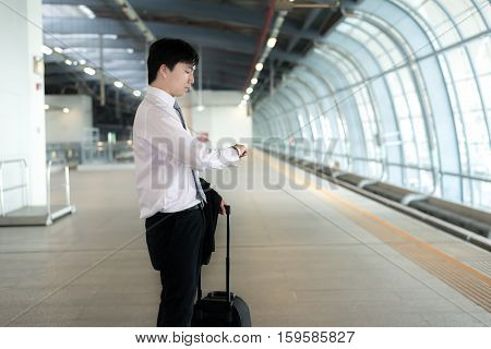 Young Asian businessman looking in his watch while waiting train delay at train station. Business travel concept.