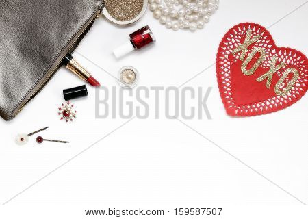 Over head flat lay view of a luxury vanity desk top. Silver, gold and red metallic. Cosmetics, jewelry, glitter, and red paper heart. Open space for text.