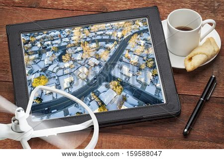 aerial photography concept - reviewing aerial pictures of city residential area in snow on a digital tablet with a drone rotor and coffee, screen picture copyright by the photographer