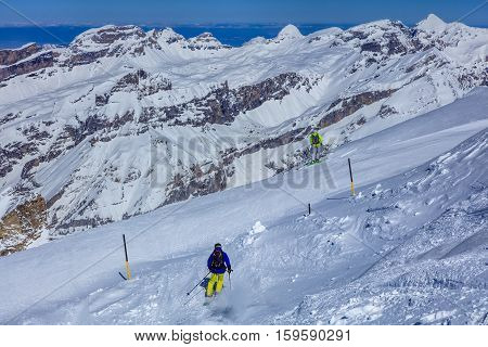 Mt. Titlis, Switzerland - 9 March, 2016: people skiing, Swiss Alps in the background. Titlis is a mountain, located on the border between Swiss Cantons of Obwalden and Bern, usually accessed from the town of Engelberg on the north side.