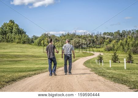 horizontal image of a caucasian father and teenage son spending quality time together talking and walking down a gravel  gravel path with lots of green grass and trees in the summer time.