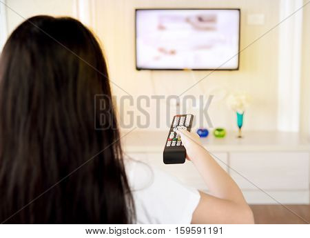 Over the shoulder view of young Asian girl with long black hair sitting on sofa holding tv remote and surfing programs on television. Teenage woman watching TV in the living room