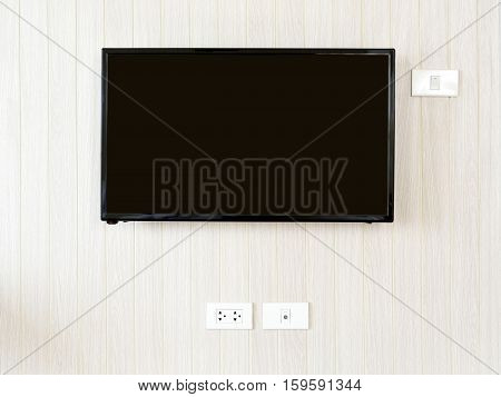 Blank lcd Flat screen television hanging at the planks wooden wall with copy space in living room or bedroom. White home electrical switch and plug outlet on a light brown or beige color wooden wall.