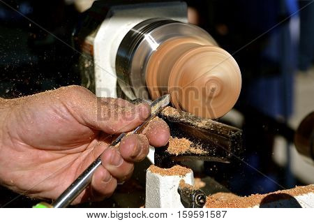 Closeup of a skilled woodworker turning wood on a lathe