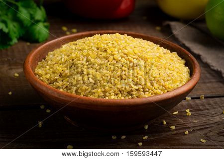 Bulgur in ceramic bowl on brown wooden table, close up view