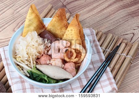 Thai noodle with pink tofu soup topped rugby fishball ,wonton,porkball, boiled porkblood ,pork rind ,coriander and white mushroom call Yen Ta Fo in Thai