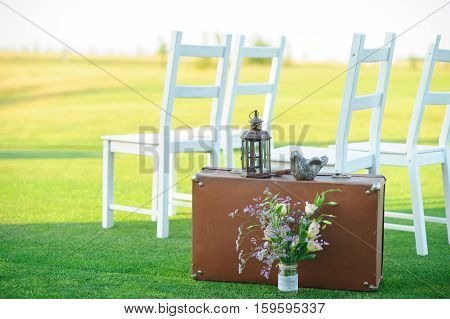 white chairs suitcase flowers lawn grass, wedding
