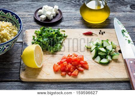 Preparation of healthy vegetable salad. Cooking ingredients on wooden cutting board. Chopped vegetables, olive oil, cheese and bulgur grains for salad tabbouleh