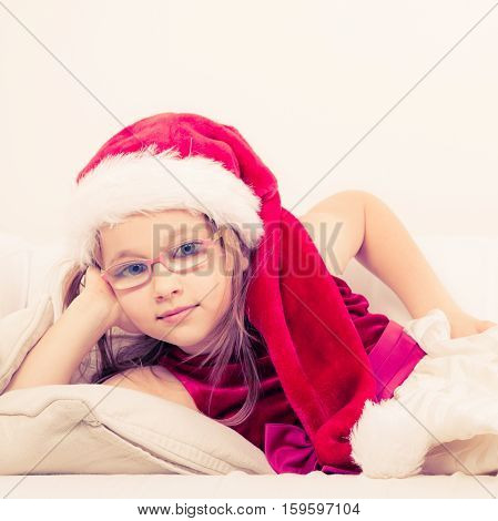 Christmas holiday concept. Toddler girl wearing Santa Claus hat and christmassy dress lying on sofa with pillows cheek propped up by hand.