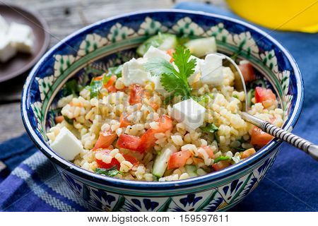 Salad with bulgur, tomato, parsley and feta cheese in bowl, close up view. Healthy, delicious, light meal