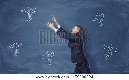 A businessman trying to catch the dollar signs with wings drawn on the blue blackboard. Making money. Success and profit. Business concept
