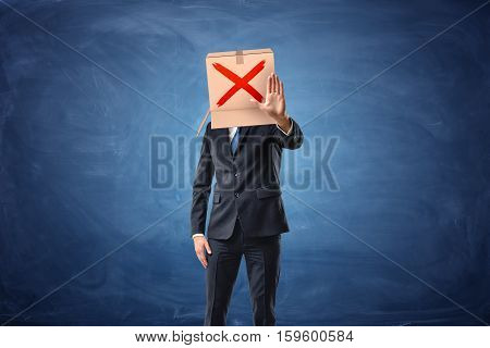 Businessman is wearing cardboard box with drawn red cross sign on it and making stop sign by his hand, on blue chalkboard background. Don't do it. Restrictions and limitations. Serious risk.
