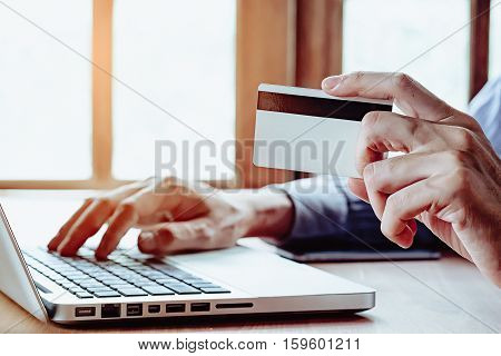 Young man hands holding a credit card and using laptop computer for online shopping.Online shopping concept.