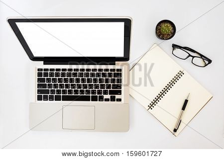 Modern White office desk table with blank screen laptop computer peneyeglasses and leather notebook. Top view with copy space.Working desk table concept.