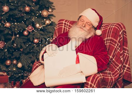 Tired Santa Claus Wearing Red Costume Sleeping And Holding Paper Roll Of Wishlist Near Pine