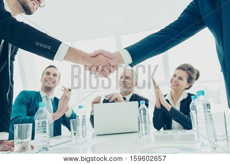 Close Up Of Two Businessmen Shaking Hands  During Meeting