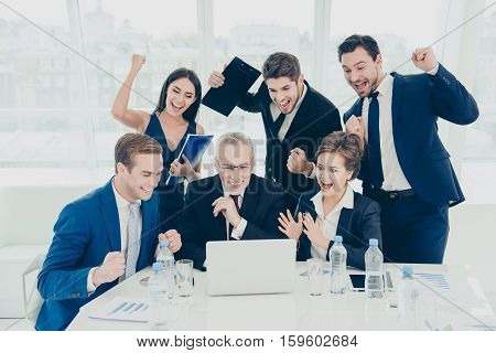 Great News! Happy Smiling Businesspeople Triumphing With Raised Fists