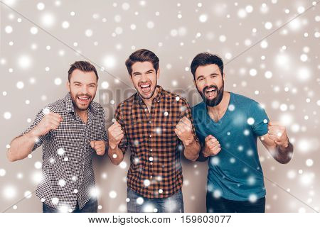 Three Handsome Screaming Men Showing Their Fists On Xmas Background