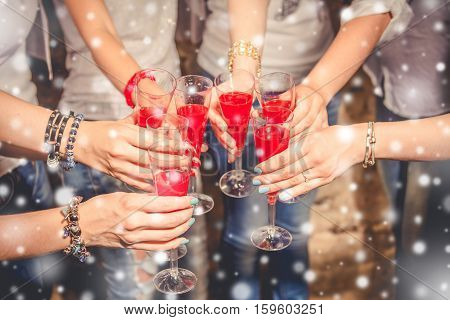 Cheers!Girls celebrating new year and clinking with glasses of red shampagne