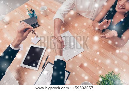 Broker Giving Keys Of New House And Handshaking With Customer On Snowy Background In Business Meetin
