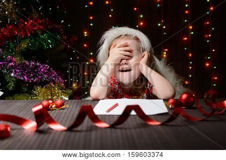 Girl Sitting In A Christmas Interior, Covering Eyes With Hands