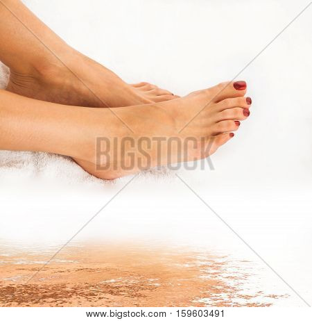 Beautiful legs of young woman with pedicure on white towel and water reflection