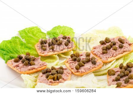 Meat pate with capers on crackers and lettuce on plate.