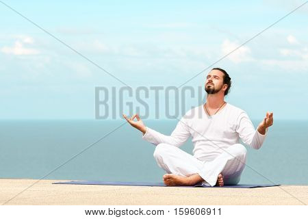 Caucasian man in white clothes meditating yoga on the sea shore pier