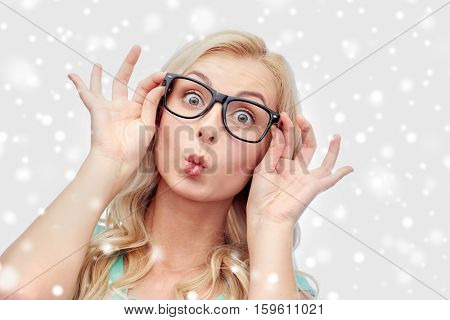 vision, education and people concept - happy young woman or teenage girl glasses making funny fish face over snow