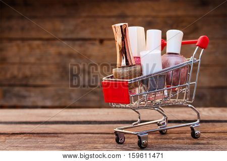 Shopping cart with nail varnish on old wood background. Toned image.