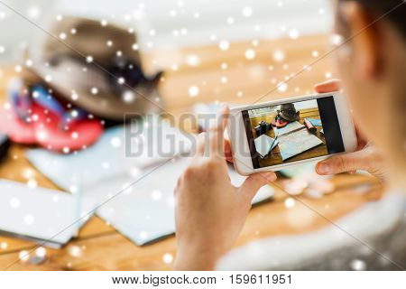 vacation, tourism, technology and people concept - close up of woman with smartphone photographing map and travel stuff