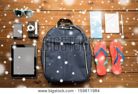 travel, tourism, winter holidays and objects concept - close up of smartphone with tablet pc computer, airplane ticket and personal stuff