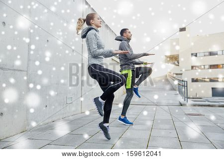 fitness, sport, people, exercising and healthy lifestyle concept - happy man and woman jumping outdoors over snow