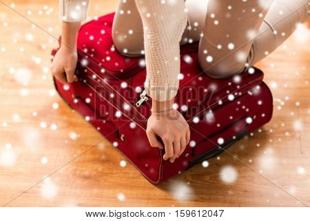vacation, travel, tourism, winter holidays and objects concept - close up of woman packing and zipping bag